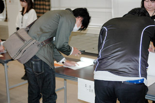 厚労省の講堂で行われた薬剤師国試の合格発表。番号を携帯電話やスマートフォンで撮影する学生が目立った