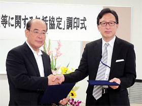 握手を交わす笠井学長(左)と林院長