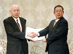 調印後、握手するAJD・杉山貞之社長(左)と全日食・平野実社長