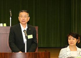 あいさつする藤垣哲彦会長ととかしきなおみ衆議院議員(右)