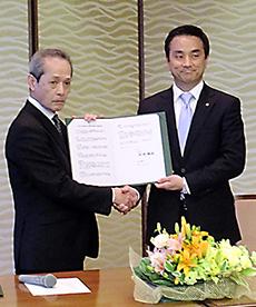 締結書を手に大野健一会長(左)と村岡嗣政知事