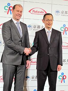 握手する武田薬品のクリストフ・ウェバー社長(左)とCiRAの山中伸弥所長