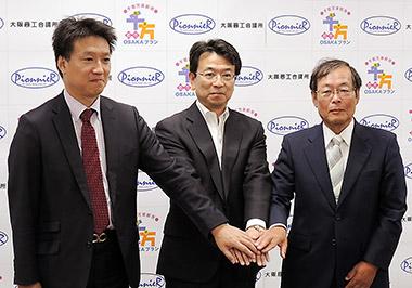 記者会見で手を取り合う相良氏(中央)、日本ベンチャーキャピタル取締役の多賀谷氏(左)、ピオニエ代表取締役の伊藤氏