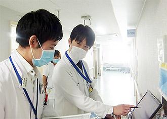 病棟で医師とカンファレンス、手前が岡田氏