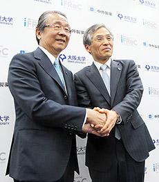 握手する左から中外製薬・永山治会長と大阪大学・西尾章治郎総長