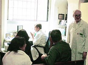 薬局内のCUP窓口で予約を待つ患者。予約端末を見ながら予約をする薬剤師は白衣を着ています