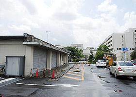 現在は車庫(左)が設置されている外来患者用駐車場の一角に、3階建ての施設が新設される