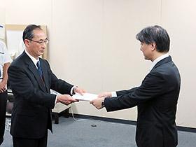 伊澤知法監視指導・麻薬対策課長(右)が処分通知を化血研の木下統晴理事に手渡した
