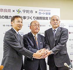 握手を交わす3氏。左から山田邦夫会長兼CEO、荒井正吾知事、竹内幹郎宇陀市長