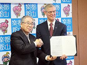 握手を交わす郡山市の品川萬里市長(左)とノボ日本法人のオーレ・ムルスコウ・ベック社長
