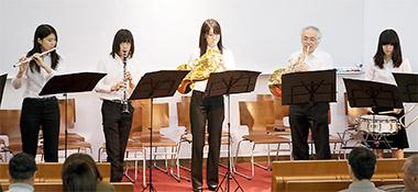 ホルンを吹く顧問の小笹さん(右から2人目)。学生と教職員が一体となって演奏する