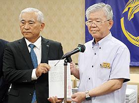 亀谷浩昌沖縄県薬会長(左)が大城肇琉球大学長に要望書と署名を手渡した